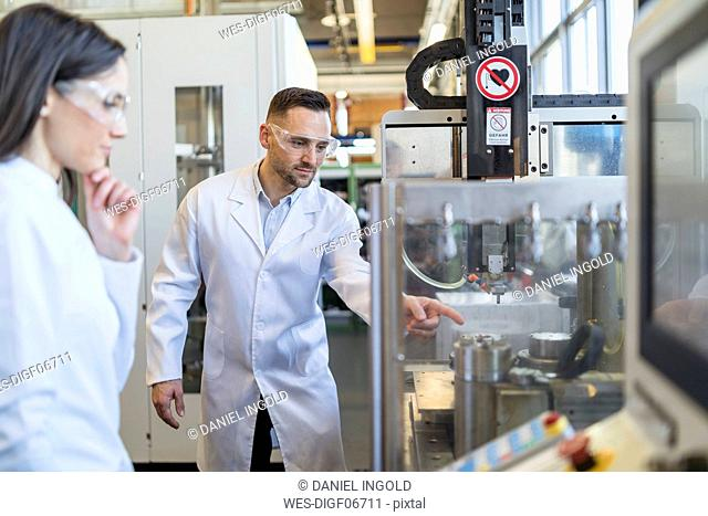 Colleagues wearing lab coats and safety goggles looking at machine in modern factory