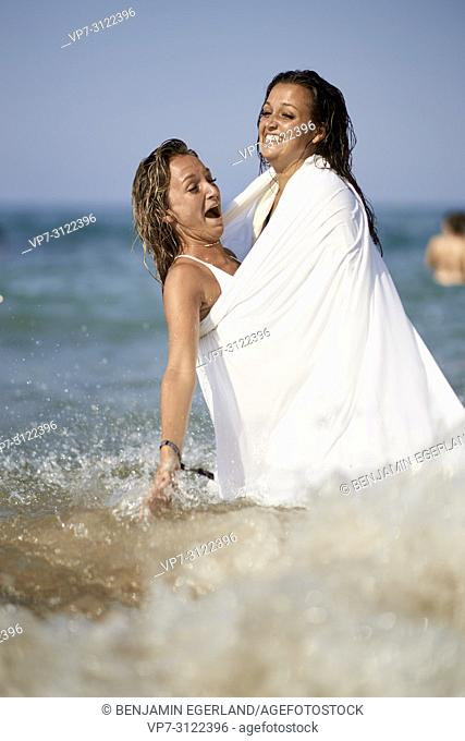 two women shrouded in white blanket sheet, playing in sea, best friends, vacations. Chersonissos, Crete, Greece