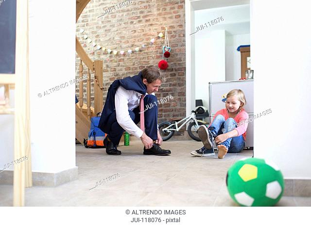 Businessman Father Getting Ready To Go To Work With Daughter