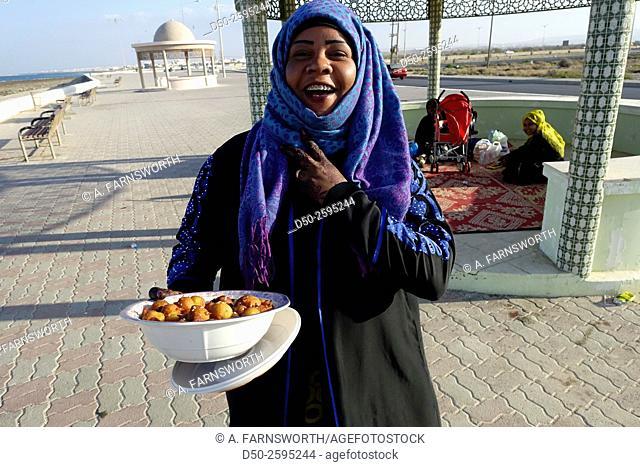 SUR, OMAN. Hospitable woman on corniche offering deep fried seet rolls like donuts