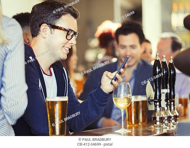 Smiling man texting with cell phone drinking wine at bar