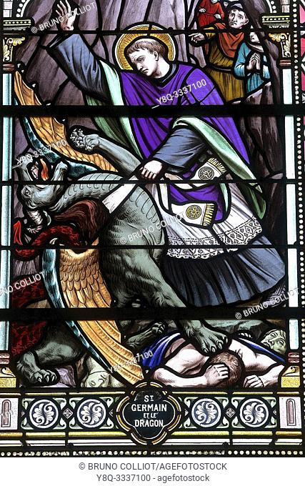 stained glass of St Germain and the Dragon in the church of Flamanville. La Manche, Normandy, France. The Baligan Hole is a coastal cave located under the...