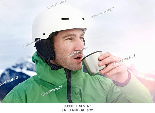 Alpinist on mountain drinking