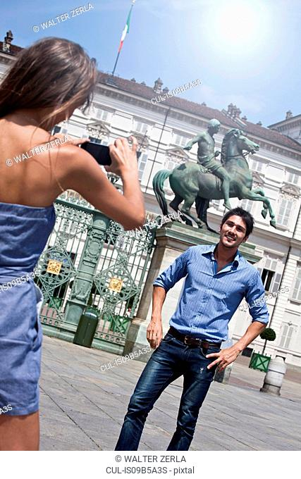 Young woman taking photograph of young man, using smartphone, Turin, Piedmont, Italy