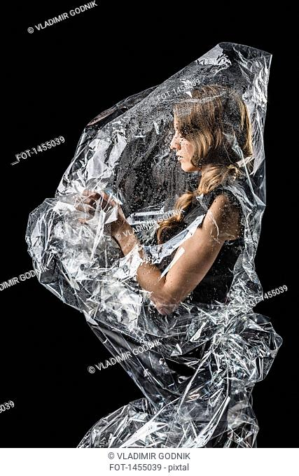 Woman wrapped in plastic standing against black background
