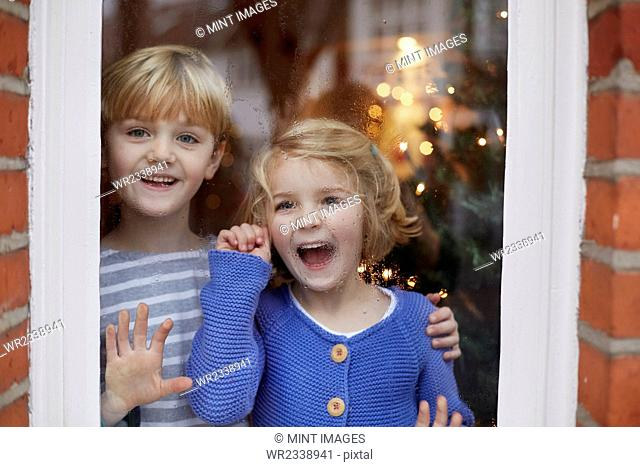 Two children, a boy and girl, looking out of a window at home with excited expressions
