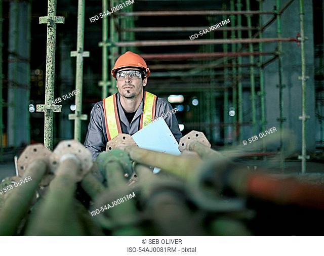 Construction worker examining pipes
