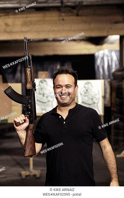 Portrait of smiling man holding a rifle in an indoor shooting range