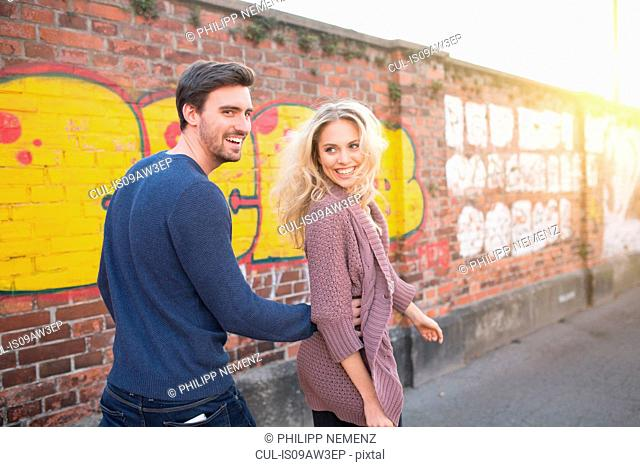 Rear view of couple walking by graffiti painted brick wall looking over shoulder smiling