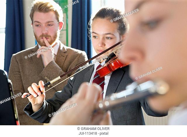 Teacher teaching high school students playing violin and flute in music class
