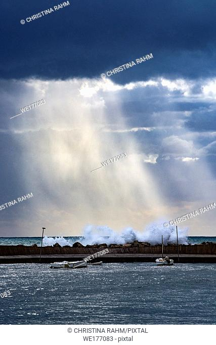 Vertical Mediterranean sea view with pier against dark skies with dramatic light on splashing waves on a winter day in Mallorca, Spain