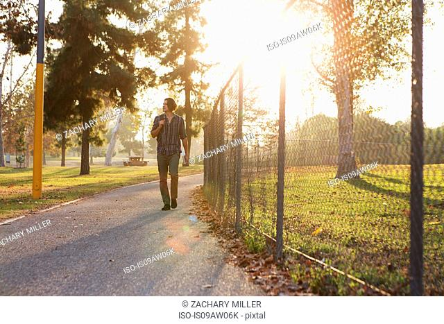 Full length front view of young man walking on pathway through park looking away