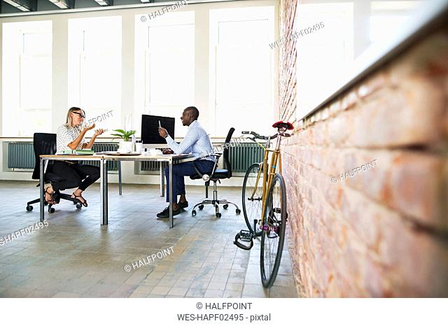 Colleagues in start-up company, sitting in office, discussing