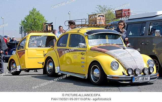 01 May 2019, Lower Saxony, Hanover: A yellow VW Beetle with trailer is parked at the 36th Maikäfertreffen on a fair parking lot