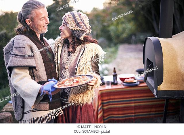 Mature hippy couple with homemade pizza in garden