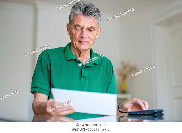 Senior man sitting at desk with paper and pocket calculator