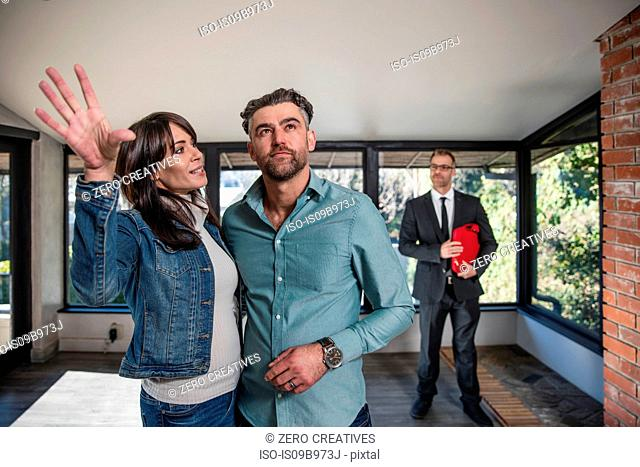 Estate agent showing couple around home, couple imagining possibilities of home