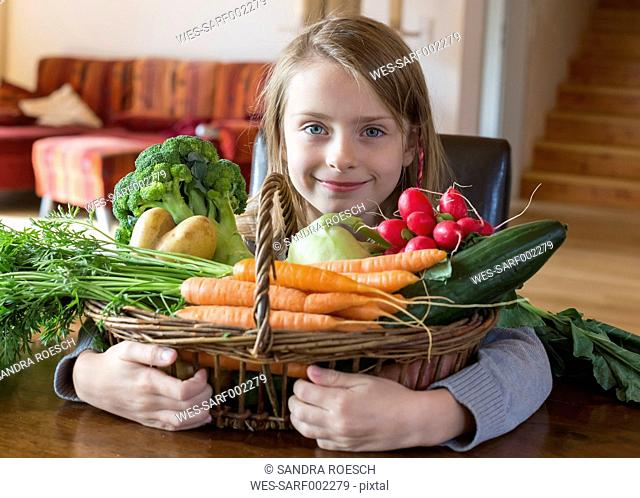 Portrait of smiling girl with wickerbasket of fresh vegetables at home