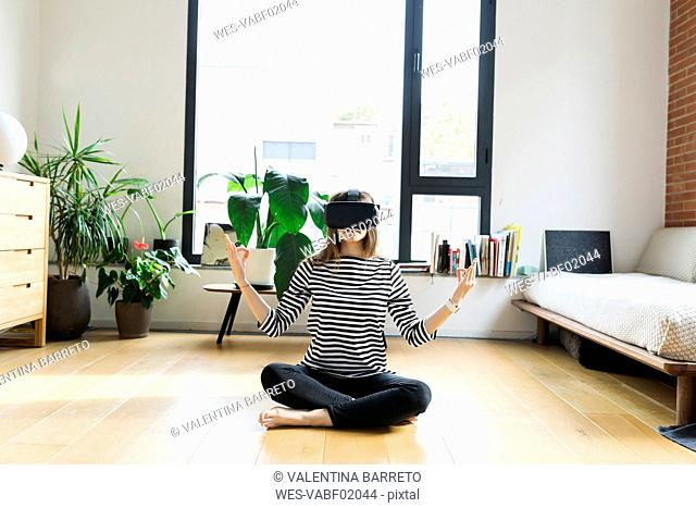 Young woman at home wearing VR glasses doing yoga