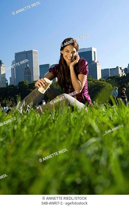 Woman with cell phone and coffee to go in Central Park, New York City, New York, USA