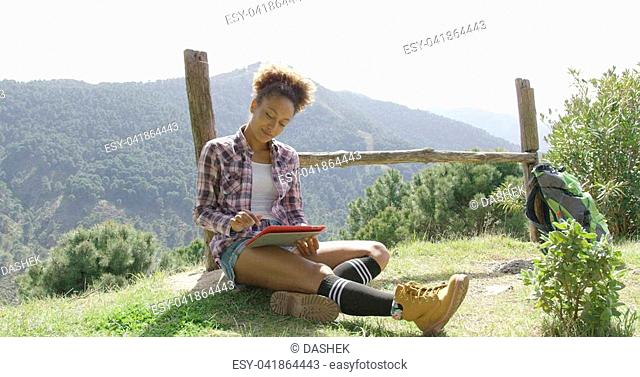 Young female sitting on ground near wooden fence using tablet on background of mountains in summer time
