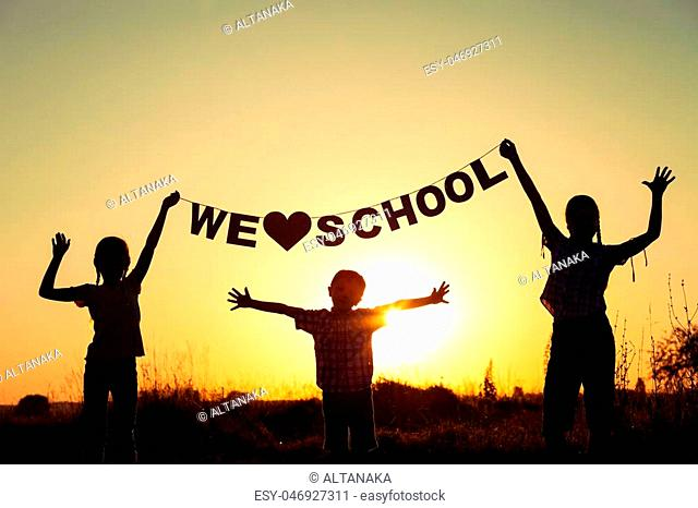 Silhouette of happy children which playing on the field at the sunset time. They having fun on the nature. Concept of the kids are ready to go to school