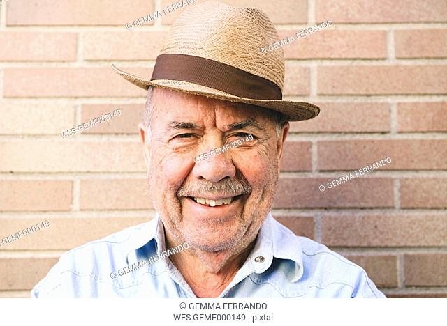 Portrait of smiling old man with straw hat