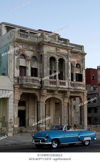 Classic Chevrolet rolls past crumbling building along the Malecon, Havana, Cuba