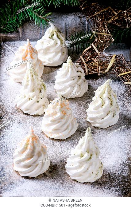 Homemade white french meringue as Christmas fir tree decorated by colored sugar and matcha tee over powdered old metal background with holiday decoration