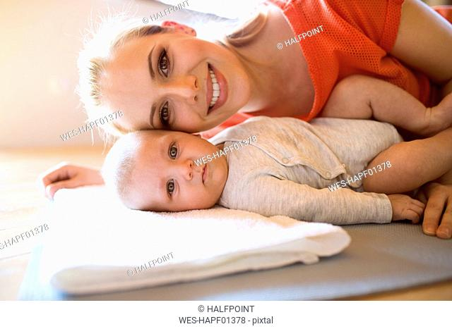 Portrait of happy mother with baby at home