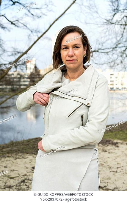 The Hague, Netherlands. Portrait of a caucasian woman in a park closing her jacket zipper