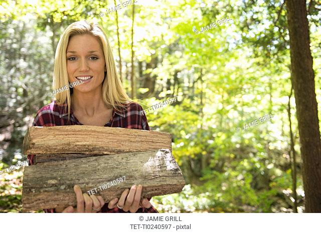 Portrait of woman holding logs in forest