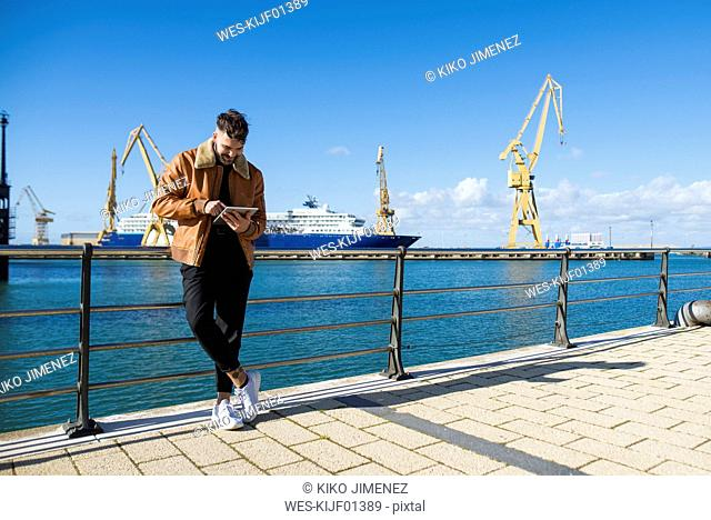 Spain, Cadiz, Young man at the harbour using digital tablet
