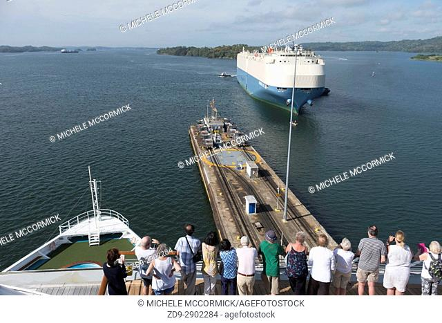 Tourists watch as ships pass through one of the locks at the Panama Canal