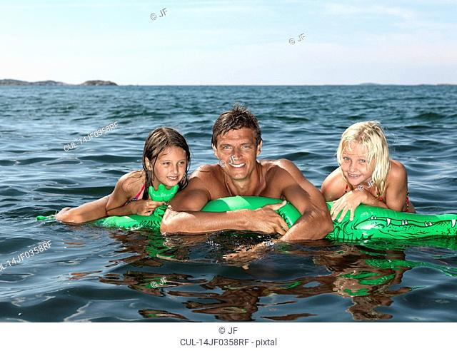 Father and girls on inflatable mattress