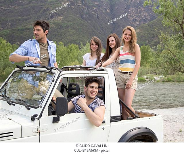 Friends standing on back of off road vehicle