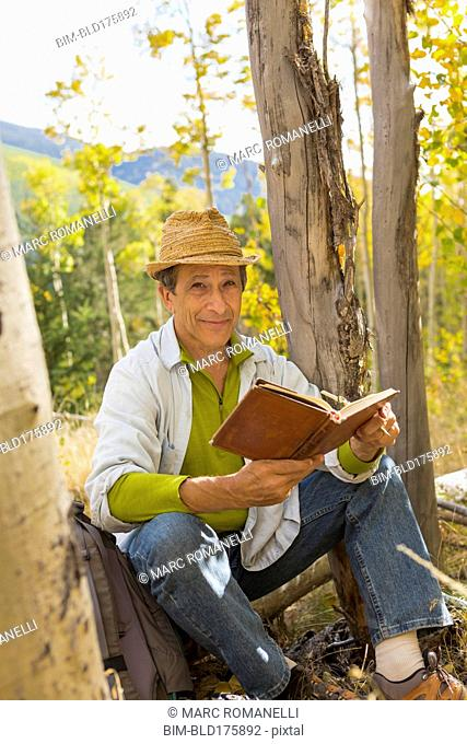 Man reading book in autumn forest
