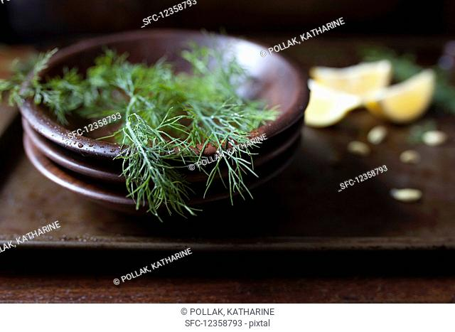 Fresh dill fronds in a wood bowl and lemon wedges