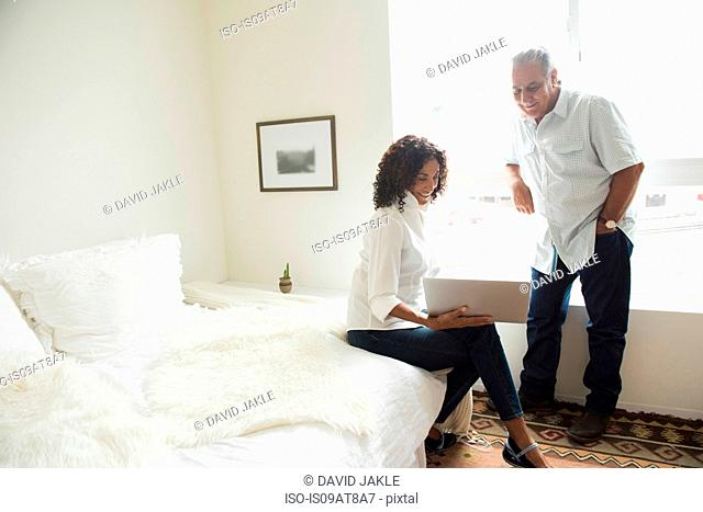 Senior man and wife looking at laptop in bedroom