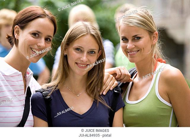 Three female teenage students smiling outdoors