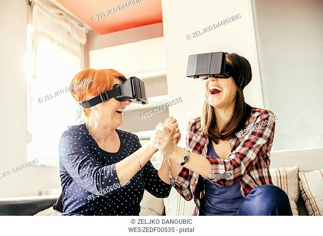 Excited adult daughter with mother at home wearing VR glasses