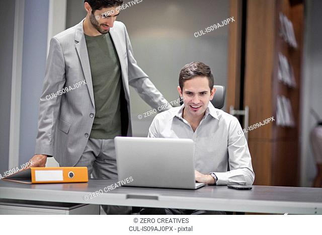 Two men in office, one using laptop