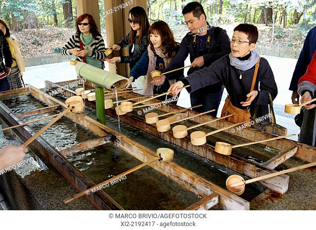 Pilgrims washing their hands and purifying, before entering the Senso-ji Asakusa Shrine. Tokyo, Japan