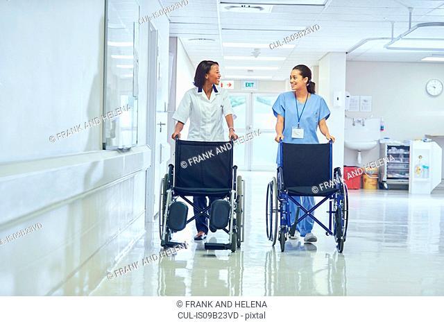 Female orderlies pushing wheelchairs along hospital corridor