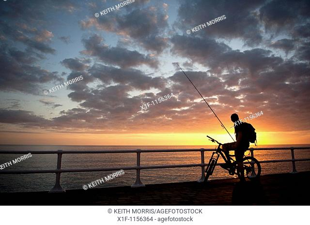 The silhouette of a young man on a bicycle at sunset, about to go fishing, cardigan bay west wales UK