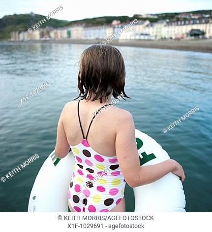 Rear view of a ten year old gilr holding her rubber ring about to go swimming in the sea, summer evening