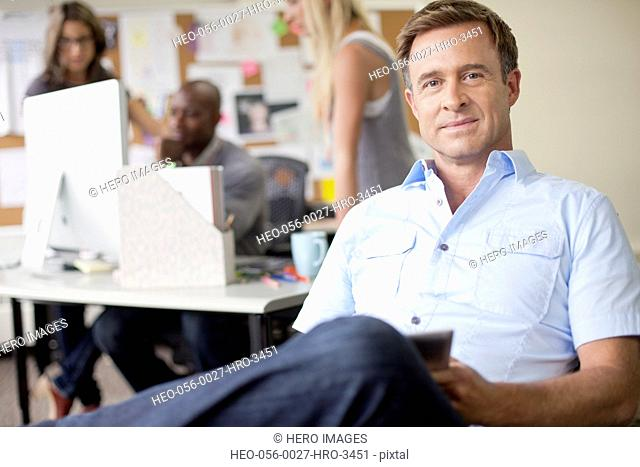 handsome, middle-aged designer in office with pc tablet