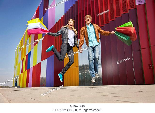 Jumping with colored shopping bags