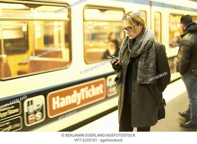 woman using smartphone in subway, Munich, Germany