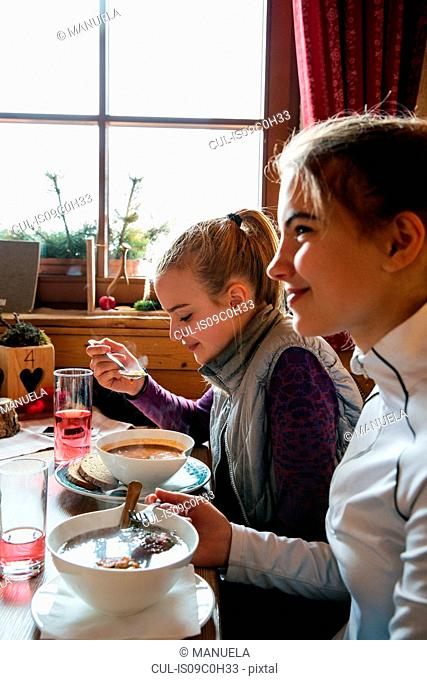 Two teenage girl skiers eating meal in cabin